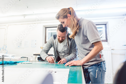 Fotografie, Obraz  Woman preparing advertisement sticker with text to be printed on a T-Shirt