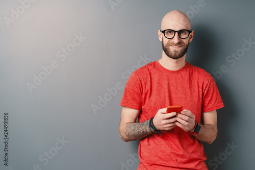 Fotografia  Handsome hairless Caucasian man with beard, glasses, red T-shirt holding smartph