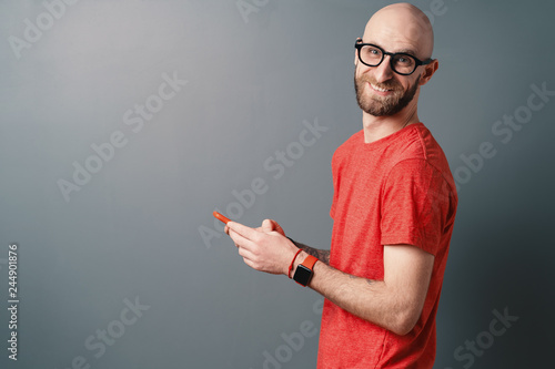 Photo  Cheerful hairless Caucasian man with beard, glasses, red T-shirt talking on the