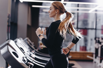 Fototapeta na wymiar The athletic girl dressed in a black sportswear running on the treadmill in the modern gym