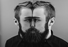 Black And White Photo Of A Man With A Beard And Stylish Hairdo Dressed In The Black Shirt Standing Next To The Mirror With Reflection Of Part Of His Face