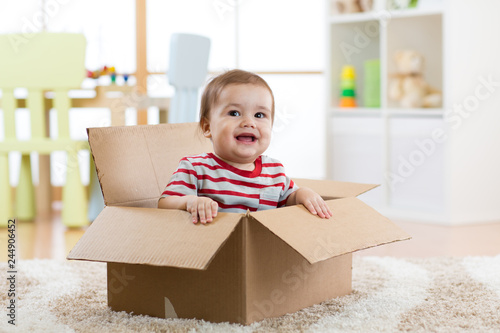 Obraz Smiling baby boy sitting inside cardboard box after moving to a new apartment - fototapety do salonu