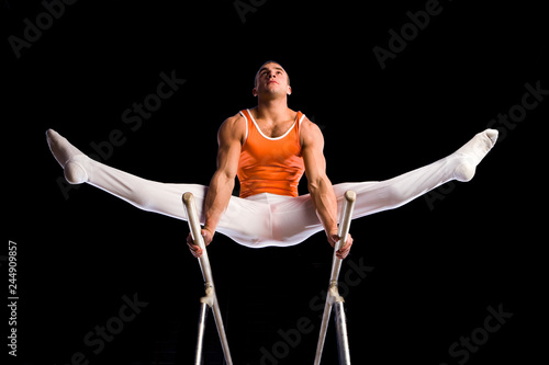 Male gymnast balancing on parallel bars against black background