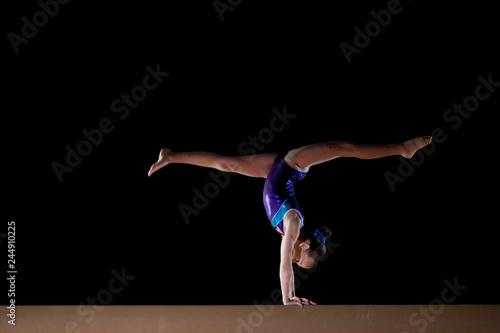 Female gymnast performing handstand on gymnastic balance beam