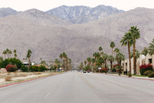 Street With Palm Trees And Mountains Of The Tahquitz Canyon In The Background In Palm Springs, California.
