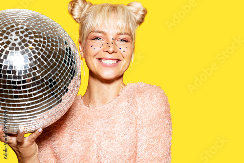 Fotografie, Obraz  Portrait of cheerful caucasian model posing in studio with silver disco ball on yellow background