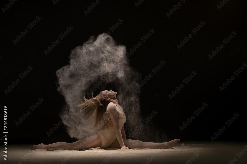 Fototapeta Brunette sitting in a split in white dust cloud