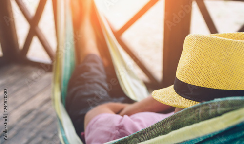 Fototapeta Young man lying in hammock at sunny beach by ocean and sleeping