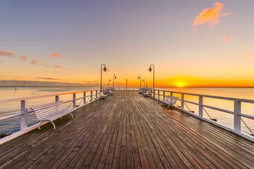 Panel Szklany Podświetlane Molo wschód słońca nad morzem