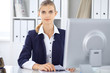 Modern business woman or confident female accountant working at pc in office. Audit, tax service or education concept
