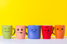 A Lot Of Multi-colored Cups With Funny Faces On A Yellow Background. The Concept Of A Friendly Company, A Big Family, Meeting Friends For A Cup Of Tea Or Coffee, Father's Day, Office, Boss Day.