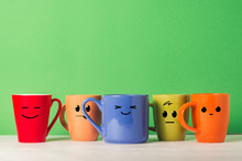 A Lot Of Multicolored Cups With Funny Faces On A Green Background. The Concept Of A Friendly Company, A Big Family, Meeting Friends For A Cup Of Tea Or Coffee, Father's Day, Office, Boss Day.