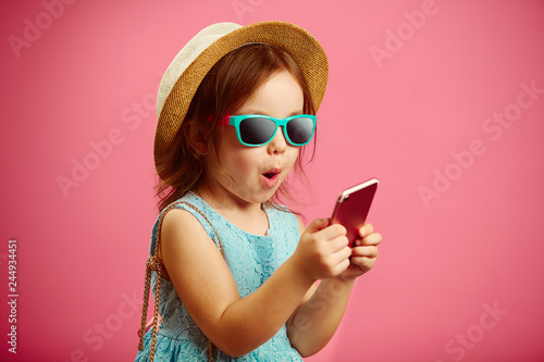 Obraz na plátne  Portrait of charming little girl in beach hat and sunglasses looking at the phone and sincerely expresses surprise, shows pleasant emotion of surprise, stands on isolated pink