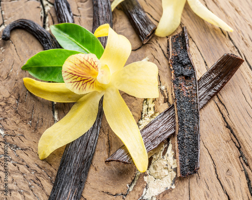 Fotobehang Orchidee Dried vanilla fruits and vanilla orchid on wooden table.