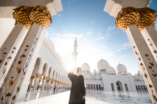 Poster Abou Dabi Traditionally dressed arabic woman standing on sun shine wearing black burka visiting Sheikh Zayed Grand Mosque in Abu Dhabi, United Arab Emirates.
