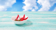 Red Chili Peper On White Plate On Blurred Sky Background