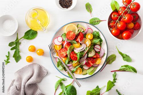 Obraz healthy colorful vegan tomato salad with cucumber, radish, onion - fototapety do salonu
