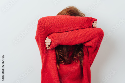 Fotografia Redhead woman hiding her face with her arms