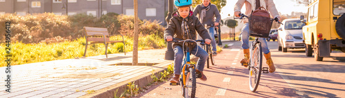 Fényképezés  Happy family with a child riding bicycles by the city on a sunny winter day