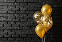 Bright Balloons Near Dark Brick Wall
