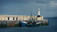Fishing Boat Moored By Pier And Lighthouse