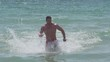 Man running out of the water on the beach in slow motion