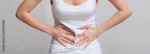 Photo Woman with stomachache, having food poisoning, grey background