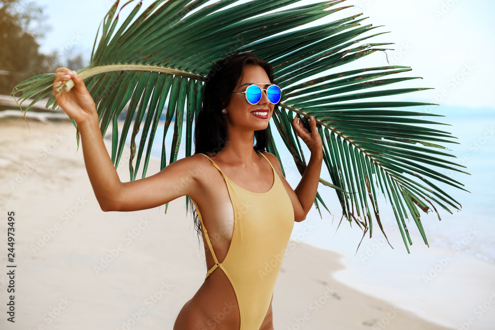 Fototapeta incredibly beautiful sexy girl models in a bikini on the sea shore of a tropical island with palm leaf, blonde brunette, bronze tan, travel summer vacation, fashion style