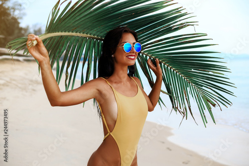 Fototapeta incredibly beautiful sexy girl models in a bikini on the sea shore of a tropical island with palm leaf, blonde brunette, bronze tan, travel summer vacation, fashion style obraz