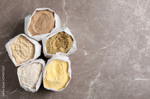 Bags with different types of flour on grey background, top view. Space for text