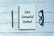 canvas print picture - Business concept. Top view of pen,glasses and notebook written with User Generated Content.