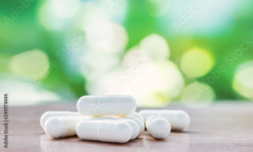 white medicine capsule on wooden table with natural background