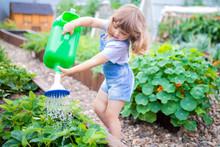 Adorable Girl Watering Plants In The Garden