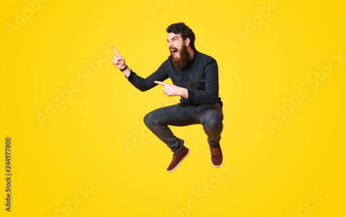 Portrait of bearded man screaming and jumping over yellow background and pointin Fototapeta