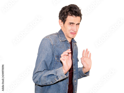 Photo  Young man with disgusted expression repulsing something