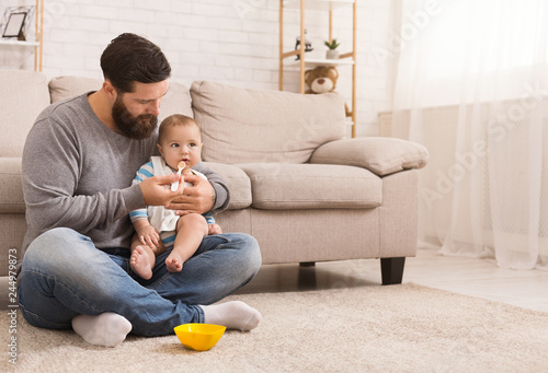 Obraz Father feeding his cute baby son at home - fototapety do salonu