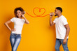 Young black couple with can phone on orange background