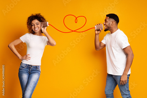 Foto Young black couple with can phone on orange background