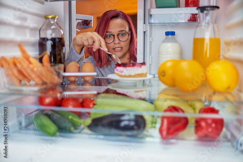 Woman standing in front of fridge an and eating cake cake. Picture taken from the inside of fridge.
