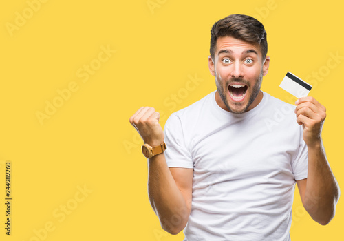 Obraz Young handsome man holding credit card over isolated background screaming proud and celebrating victory and success very excited, cheering emotion - fototapety do salonu