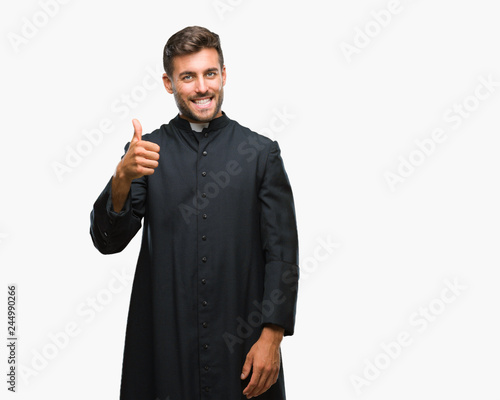 Young catholic christian priest man over isolated background doing happy thumbs up gesture with hand Wallpaper Mural