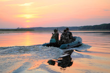 Duck Hunt. Hunters Sailing On The River In A Boat At Sunrise