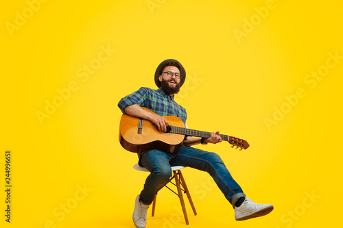 Valokuva  Trendy hipster playing guitar and singing