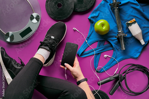 Young woman with mobile phone and sport equipment on color background flat lay top view. Fitness concept