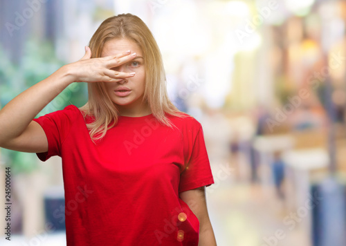 Canvas Prints Textures Young caucasian woman over isolated background peeking in shock covering face and eyes with hand, looking through fingers with embarrassed expression.