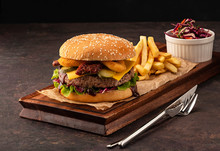 Juicy Homemade Cheeseburger In A Black Bun With Onion Rings And Dried Tomatoes. Beef Burger With Cheese And Salad.