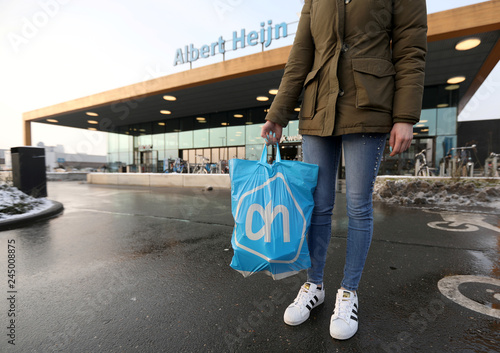 A woman holds a bag with the logo of Albert Heijn, operated
