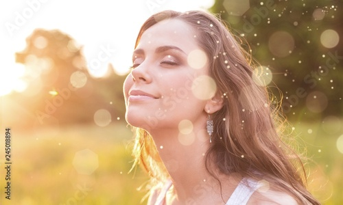 Young woman on field under sunset light Wallpaper Mural