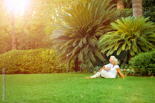 Poster Palmier Portrait of happy senior couple sitting on green meadow