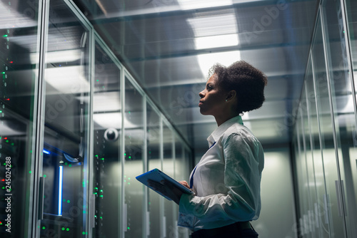 Stampa su Tela Medium shot of female technician working on a tablet in a data center full of ra